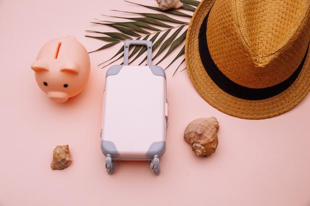 Risparmia denaro per il turismo. mini valigia da viaggio con salvadanaio sul tavolo rosa con accessori.
