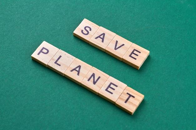 Salvare il concetto di pianeta. preoccupazione ambientale e risparmio della terra. cubi di legno con lettere isolate su sfondo verde.
