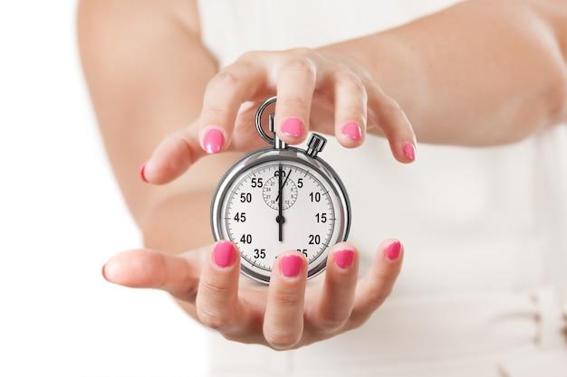 Risparmia tempo concetto. due mani della donna che proteggono il cronometro su una priorità bassa bianca.