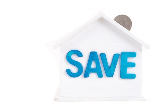 Salvare la parola sulla casa è bianco salvadanaio con monete su bianco