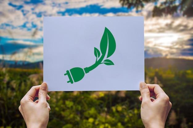 Salva il concetto di ecologia mondiale la conservazione ambientale con le mani che tengono la spina di alimentazione della carta tagliata che mostra