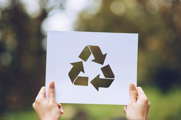 Conservi la conservazione ambientale di concetto dell'ecologia del mondo con le mani che tengono la rappresentazione tagliata di riciclaggio di carta