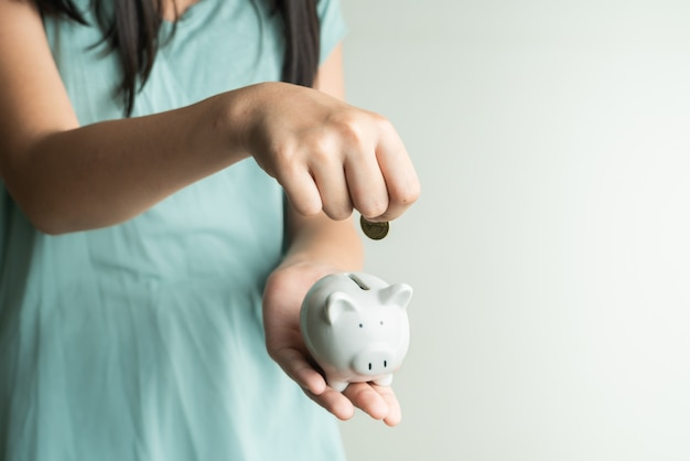 Concetto di affari e di risparmio, ragazza sveglia con il porcellino salvadanaio e monete a casa