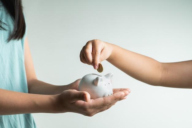 Concetto di affari e di risparmio, bambina due con il porcellino salvadanaio e monete a casa