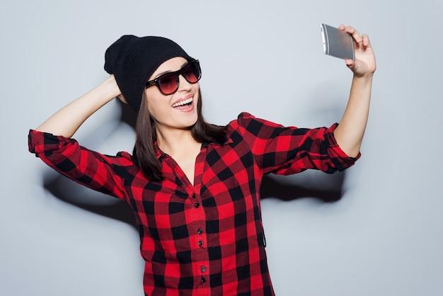 Salvataggio della memoria del suo nuovo stile. ritratto di bella giovane donna con gli occhiali che si aggiusta il cappello mentre fa selfie e sta in piedi su sfondo grigio gray