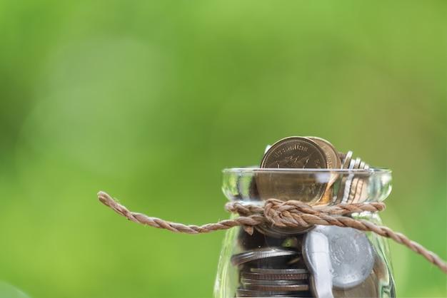Concetto dei soldi di risparmio, monete in barattolo di vetro sulla tavola di legno