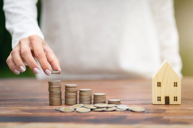 Risparmio di denaro concetto, mano femminile che mette soldi moneta pila attività in crescita.