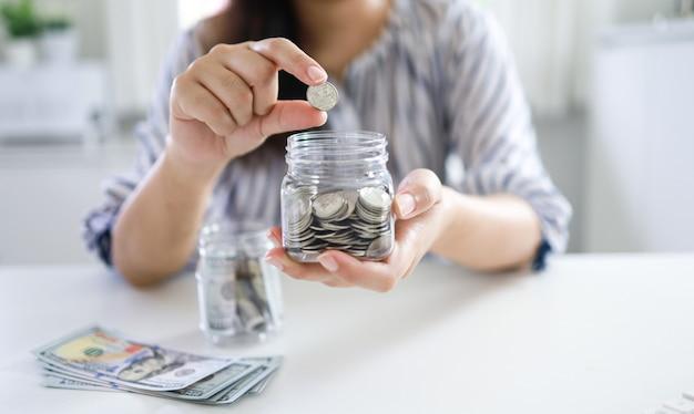 Risparmio di denaro concetto. la pila della mano della donna finanziaria conia le banconote dei soldi in crescita del business
