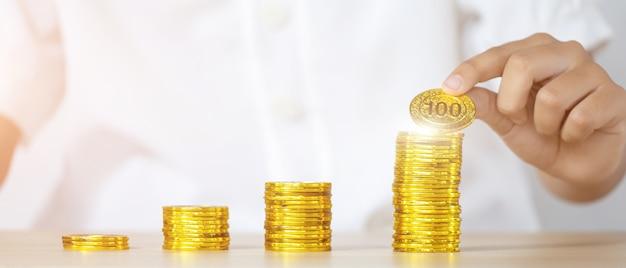 Risparmio di denaro concetto preimpostato dalla mano della donna di affari che mette la pila della moneta dei soldi, affari in crescita
