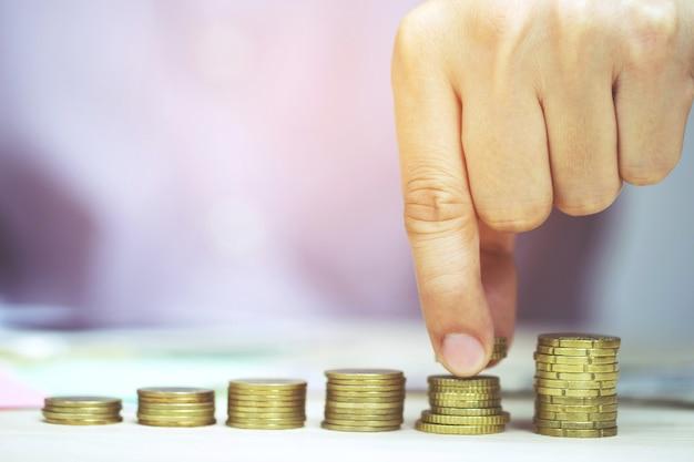 Risparmio di denaro concetto preimpostato dalla mano maschio che mette soldi moneta pila attività in crescita