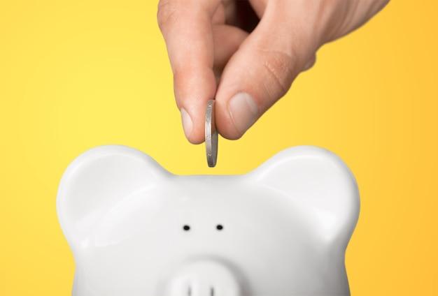 Concetto di risparmio di denaro, salvadanaio bianco con moneta da tenere in mano umana