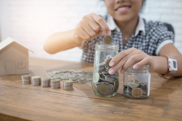 Risparmio di denaro e finanze concetto con la ragazza che mette le monete in vetro brocca