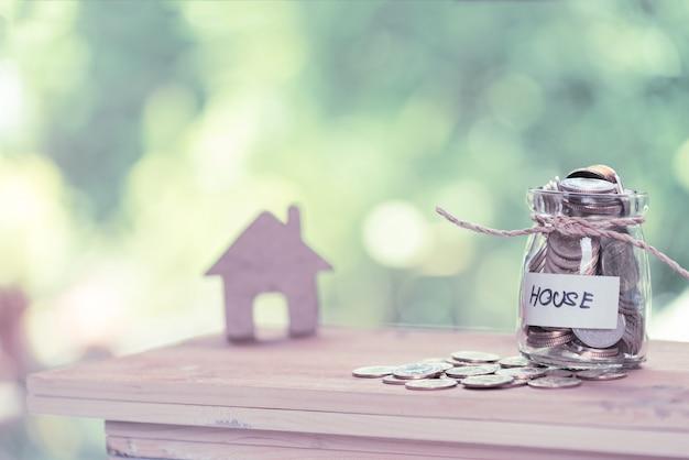 Soldi di risparmio per la casa, monete in barattolo di vetro con la casa di preventivo sulla tavola di legno