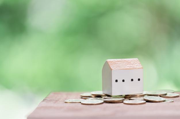 Risparmio di denaro per casa, monete d'oro e modello di casa sul tavolo di legno