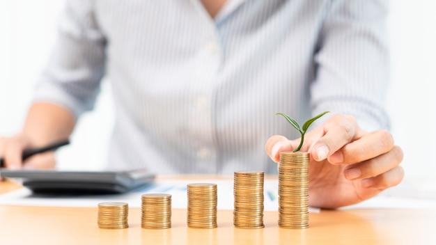 Risparmio di denaro e concetto di investimento, donna contabile di affari che impila monete in colonne crescenti impilare per budget dietro la scrivania con grafici incentrati sui soldi
