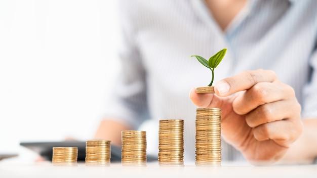 Risparmio di denaro e concetto di investimento, donna contabile di affari che impila monete in colonne crescenti impilare per budget dietro la scrivania con grafici incentrati sui soldi.