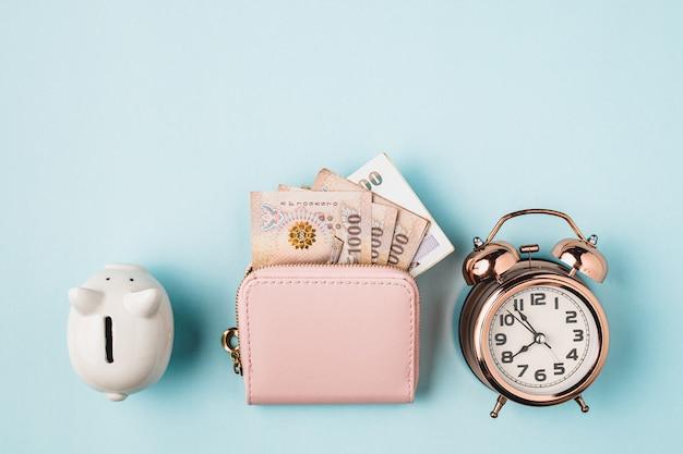 Salvadanaio salvadanaio con portafoglio di valuta thailandese, 1000 baht, banconota dei soldi della thailandia e sveglia con campana su sfondo blu per affari, finanza e concetto di gestione del tempo