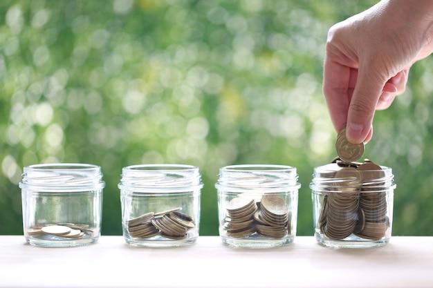 Risparmio per prepararsi in futuro e concetto di investimento aziendale, mano della donna che mette una moneta nella bottiglia di vetro su sfondo verde, finanza green