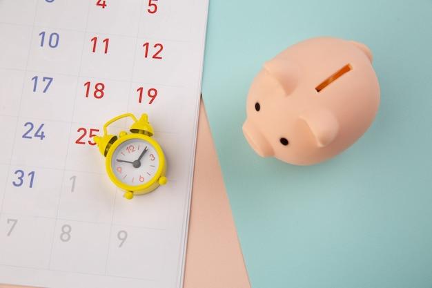 Concetto di risparmio. salvadanaio e sveglia con calendario su sfondo colorato.