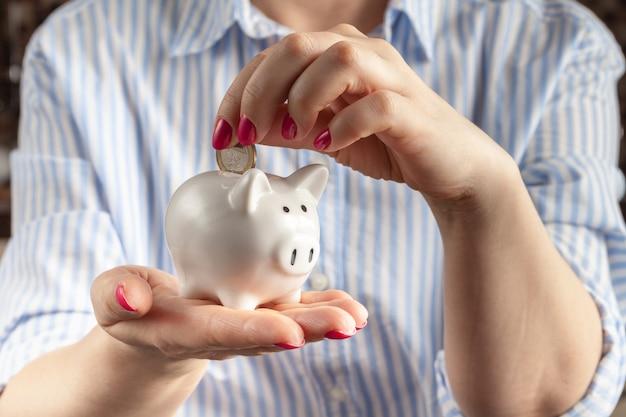 Concetto di risparmio, porcellino salvadanaio bianco con la mano femminile umana che inserisce moneta dentro