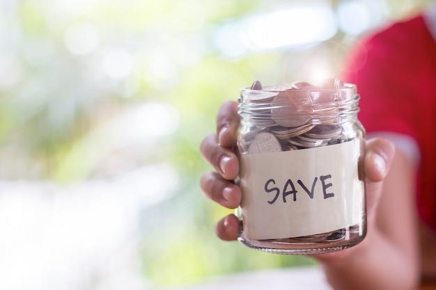 Monete di deposito di risparmio in una bottiglia di vetro trasparente