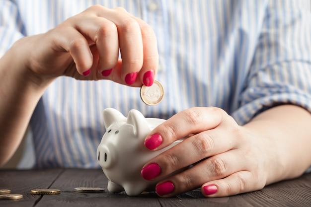 Risparmio, soldi, assicurazione dell'annualità, pensione e concetto della gente - vicino su della mano senior della donna che mette moneta nel porcellino salvadanaio
