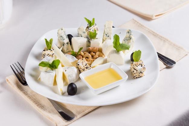 Antipasti salati guarniti con erbe fresche serviti con anacardi e una gustosa salsa cremosa per essere gustati come finger food gourmet