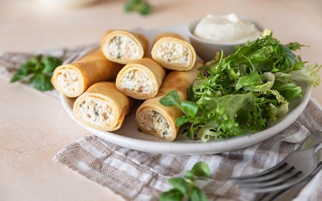 Crepes salate o frittelle sottili con pollo servite con insalata verde e salsa besciamella