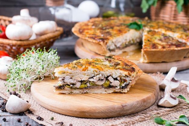 Torta salata con pollo, funghi e formaggio sul tavolo di legno