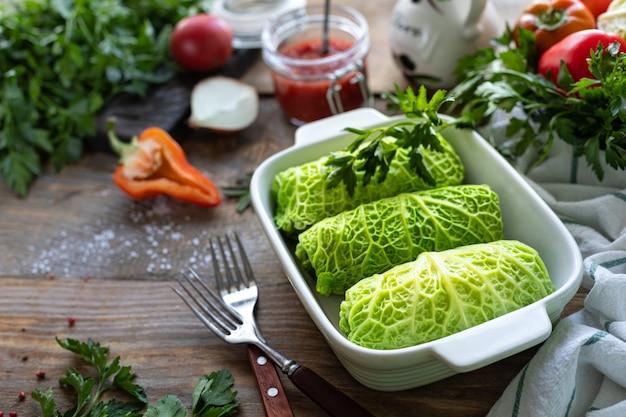 Involtini di verza ripieni di carne, riso e verdure su un tavolo rustico.