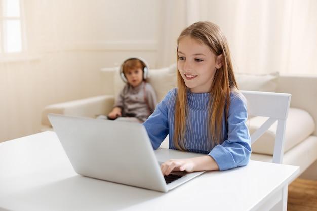 Esperta signora intelligente e ispiratrice seduta al tavolo e digitando qualcosa mentre usa il computer per completare il suo compito