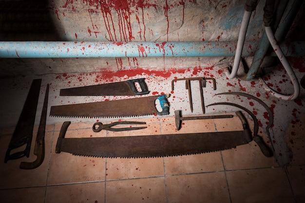 Seghe, pinze e altri dispositivi sul pavimento insanguinato nel seminterrato con tubi e fili in un concetto horror di halloween