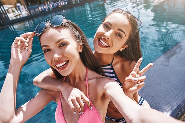 Dì formaggio gioiose e carine giovani donne in costume da bagno che fanno selfie e sorridono stando in piedi