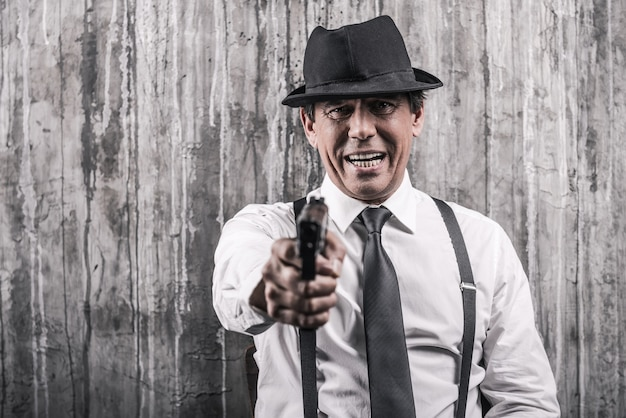 Dire addio! uomo anziano prepotente in abiti da gangster che allunga la mano con la pistola mentre si trova contro il muro grigio