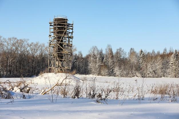 Impalcatura intorno alla torre dell'acqua nel campo di fronte alla foresta