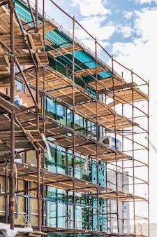 Ponteggi e impalcature con ponti in legno, contro un cielo blu. esecuzione di lavori di costruzione in quota. sicurezza della costruzione.