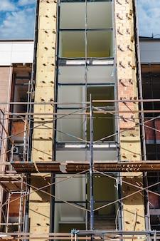 Ponteggi e ponteggi con impalcati in legno, durante la ricostruzione dell'edificio. esecuzione di lavori di costruzione in quota. sicurezza della costruzione.