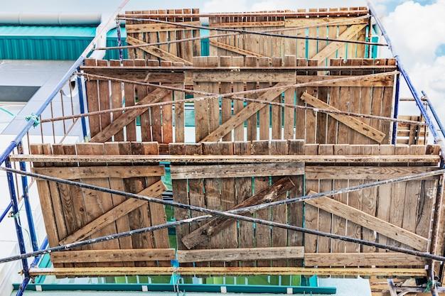 Ponteggio con ponti in legno, vista dal basso. esecuzione di lavori di costruzione in quota. sicurezza della costruzione.