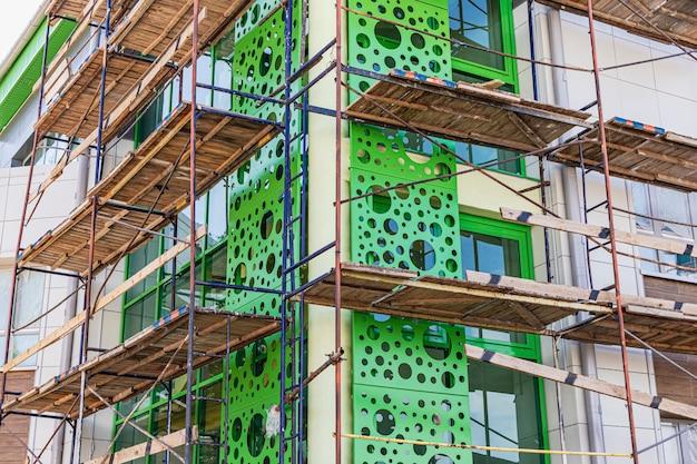 Impalcature con ponti in legno. esecuzione di lavori di costruzione in quota. guaina della facciata ventilata con metallo.