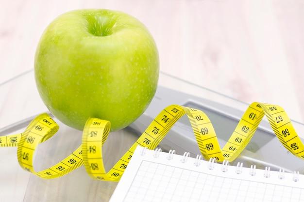 Bilance, una mela verde, un metro e un quaderno per scrivere su una superficie di legno chiaro. preparazione per la stagione estiva e il concetto di spiaggia, perdita di peso e sport