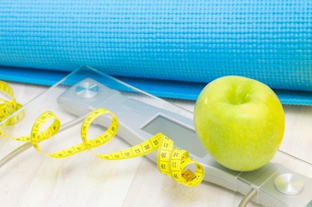 Bilance, mela verde, metro a nastro, borraccia e tappetini sportivi su una superficie in legno chiaro. perdita di peso e concetto di sport