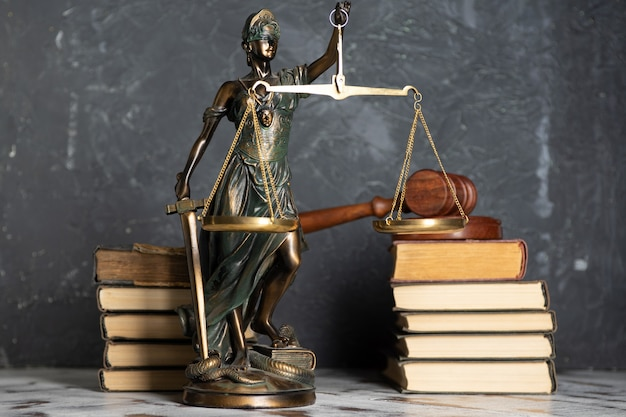Bilancia della giustizia, lady justice, concetto di biblioteca di diritto, libri di diritto sullo sfondo.