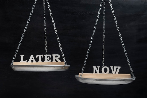 Bilancia con le parole later e now. equilibrio su sfondo nero