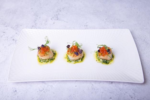 Capesante con microgreens di caviale e salsa verde su un piatto bianco