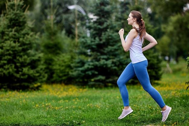 Scamper di donna europea snella in un parco pubblico