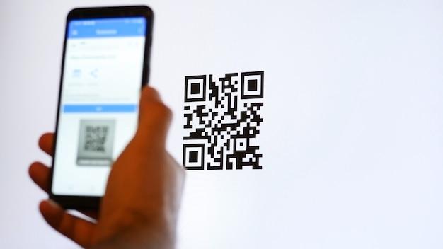 Scansiona il codice qr con lo smartphone sul monitor del computer. Foto Premium