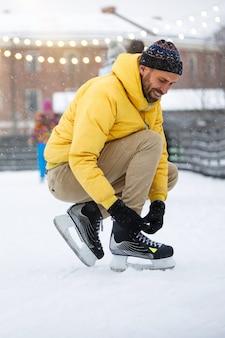 Uomo barbuto scandinavo che lega i pattini neri sulla pista di pattinaggio nel giorno di inverno nevoso