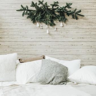 Camera da letto scandinava con lenzuola bianche con decorazioni natalizie fatte di rami di abete e giocattoli bianchi