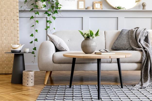 Concetto scandinavo dell'interno del soggiorno con divano di design, tavolino, pianta in vaso, fiori, tappeto, plaid, cuscino, mensola, decorazione e accessori personali nella moderna messa in scena della casa.
