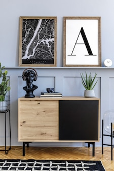 Interiore della casa scandinava del soggiorno con due finte cornici per poster, comò in legno, orologio, piante, decorazioni, tappeti e accessori eleganti in un elegante arredamento per la casa.